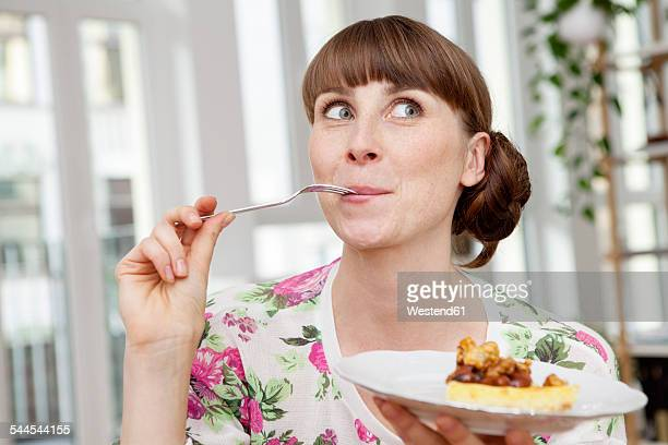 smiling woman enjoying piece of cake - food and drink stock pictures, royalty-free photos & images