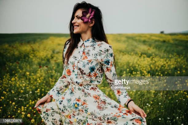 mulher sorridente curtindo o dia ensolarado de verão na natureza - vestido comprido - fotografias e filmes do acervo