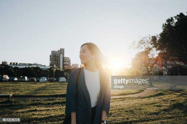 Smiling woman enjoying the beautiful sunset in a park