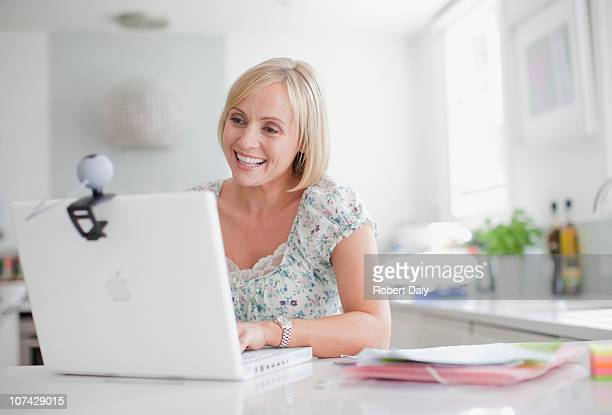 smiling woman enjoying video chat on laptop - webcam stock pictures, royalty-free photos & images