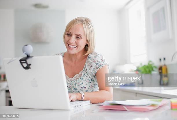 Lächelnde Frau, die video-chat auf laptop