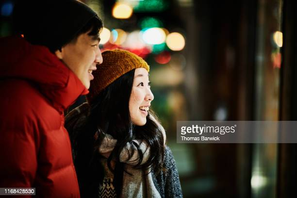 smiling woman enjoying window display while holiday shopping with husband on winter evening - holiday stock pictures, royalty-free photos & images