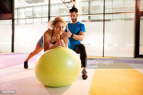 Smiling woman exercising on fitness ball with person trainer.