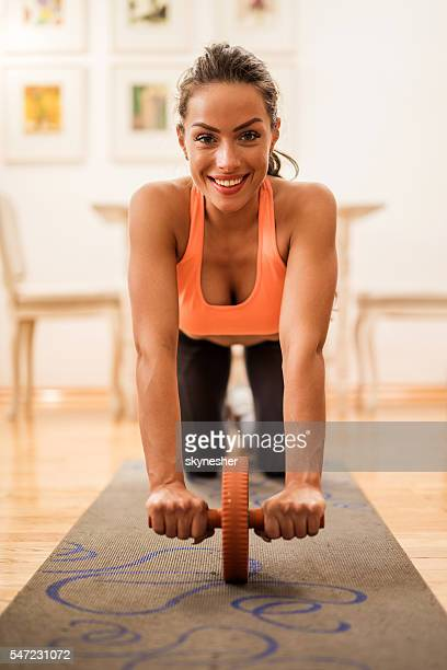 Smiling woman exercising with abdominal muscle wheel at home.
