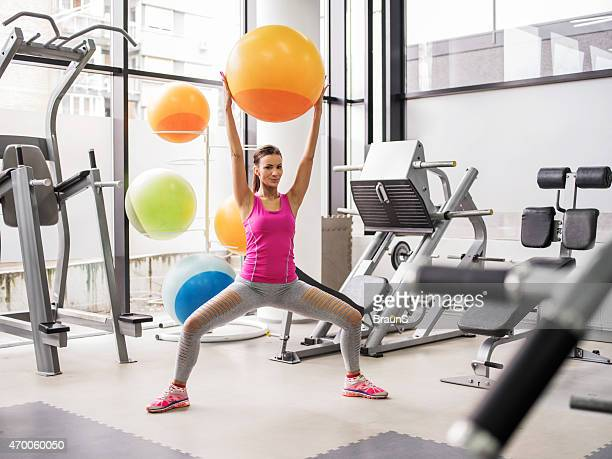 Smiling woman exercising with fitness ball in a health club.