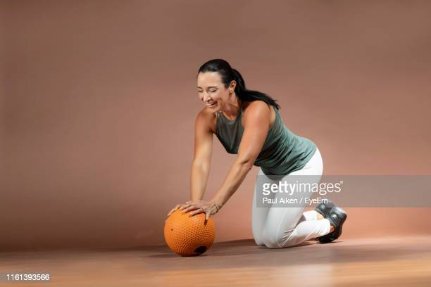 smiling woman exercising with medicine ball against wall - aikāne stock pictures, royalty-free photos & images