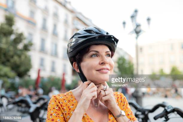 smiling woman fastening cycling helmet in city - madrid stock pictures, royalty-free photos & images