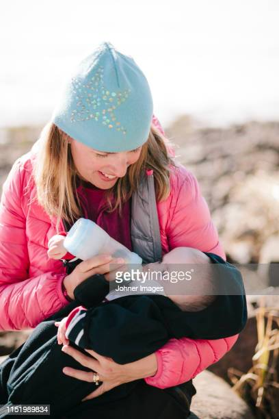 smiling woman feeding baby - norrbotten province stock pictures, royalty-free photos & images