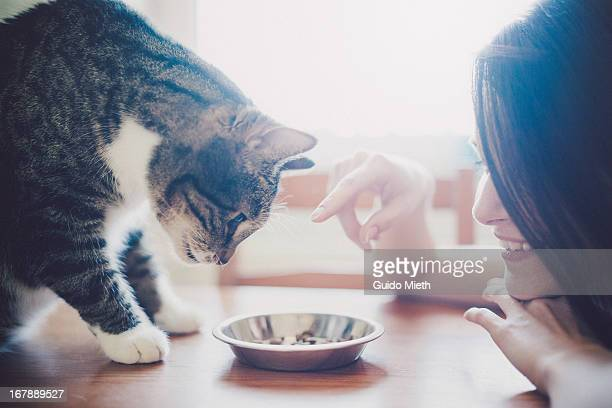 Smiling woman feeding her cat.