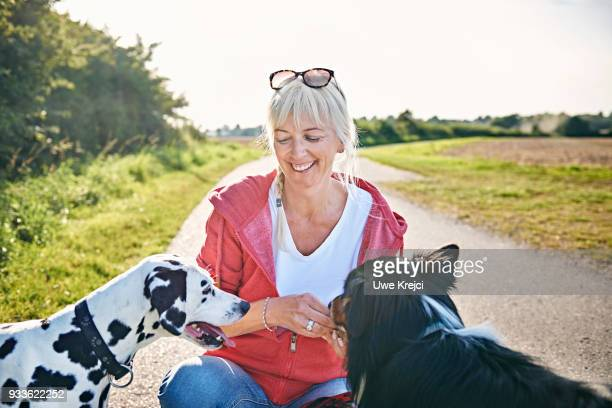 Smiling woman feeding her dogs on dog walk