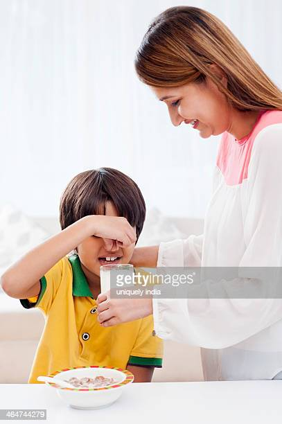 Smiling woman feeding milk to her son