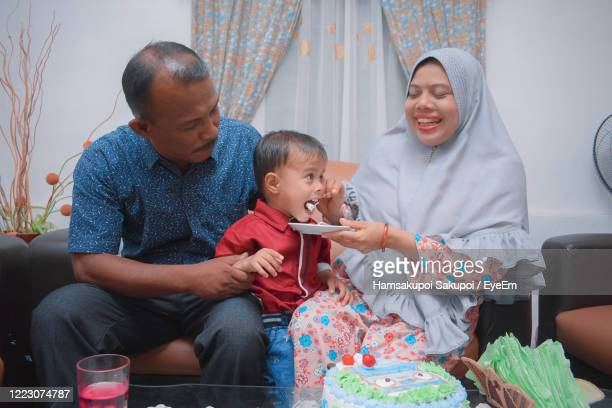 smiling woman feeding son held by father at home - hamsakupoi stock pictures, royalty-free photos & images