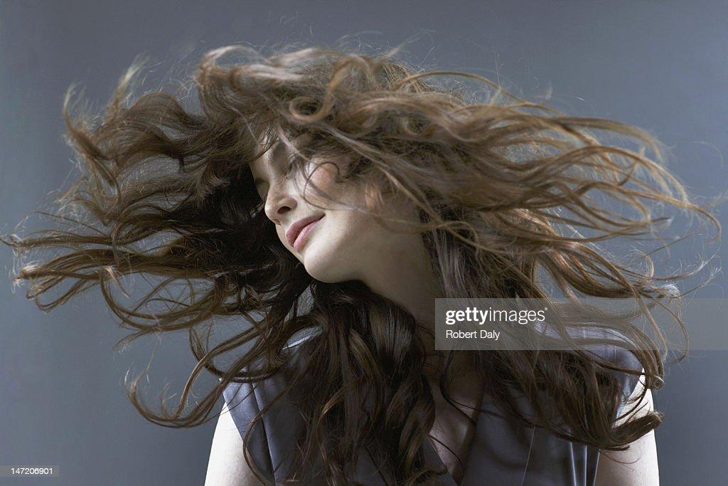 Smiling woman flipping hair : Stock Photo