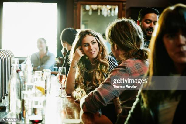 smiling woman flirting with man while sitting in bar - comptoir de bar photos et images de collection