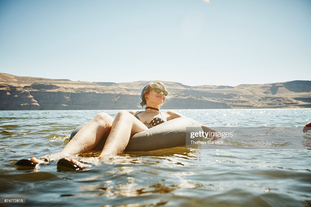 Smiling woman floating in inner tube in river : Stock Photo