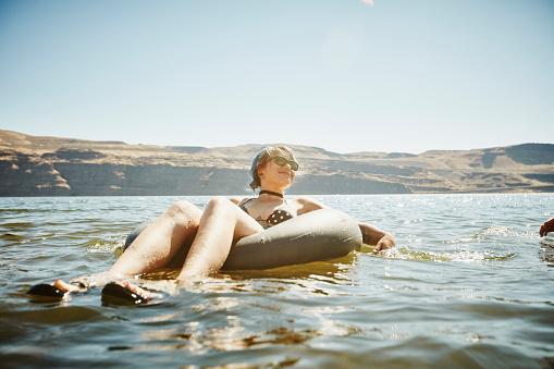 Smiling woman floating in inner tube in river - gettyimageskorea
