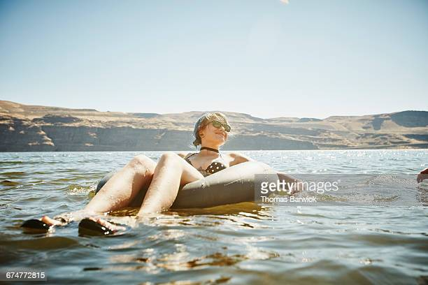 smiling woman floating in inner tube in river - carefree stock pictures, royalty-free photos & images