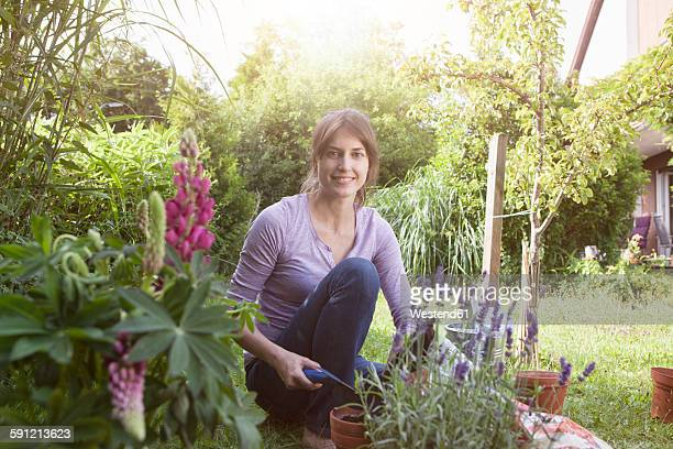 Smiling woman gardening in flowerbed