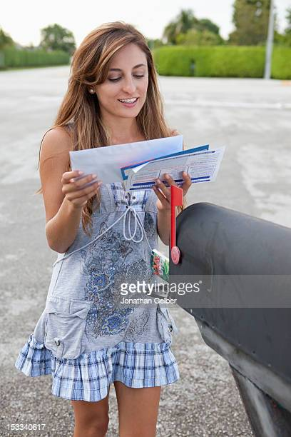 a smiling woman getting her mail from a mailbox - domestic mailbox stock pictures, royalty-free photos & images