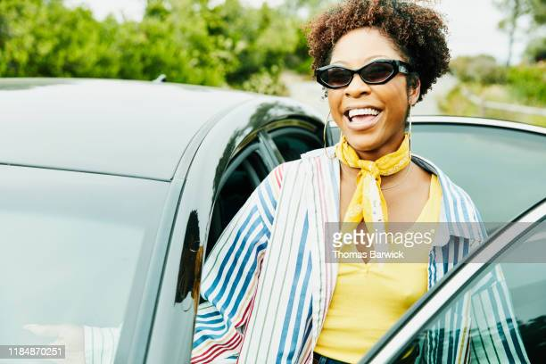 smiling woman getting into drivers seat of car before road trip - ネッカチーフ ストックフォトと画像