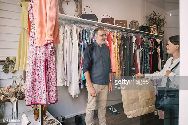 Smiling woman giving bag to man standing at thrift store