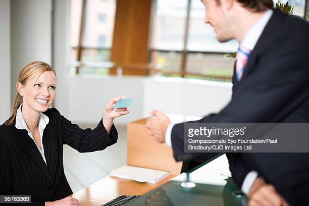 Smiling woman giving business man a card