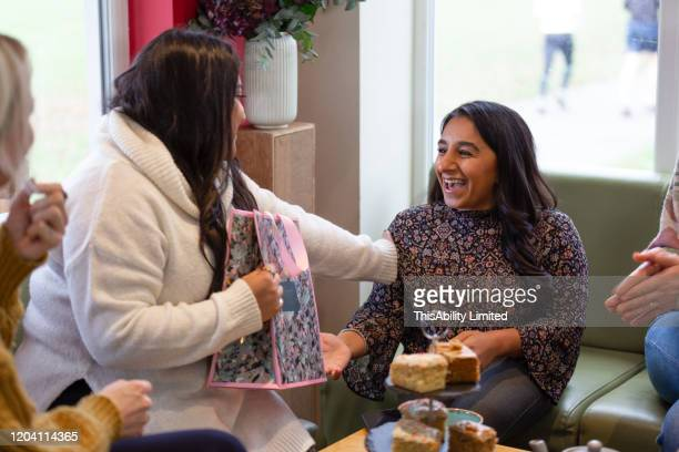 smiling woman giving gift to her friend in cafe - giving stock pictures, royalty-free photos & images