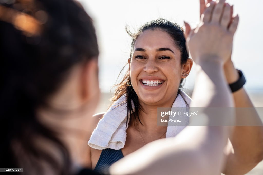 Smiling woman giving high five to her friend after exercising : Stock-Foto