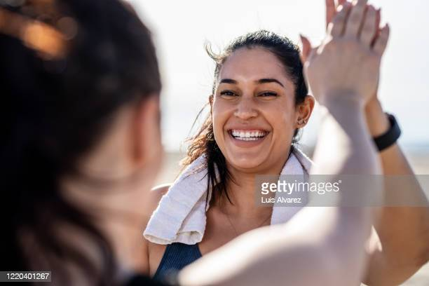 smiling woman giving high five to her friend after exercising - confidence stock pictures, royalty-free photos & images