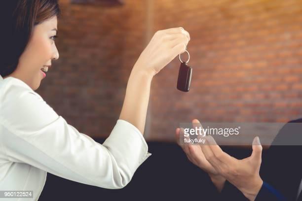 smiling woman giving key to man - homem pegando mulher imagens e fotografias de stock