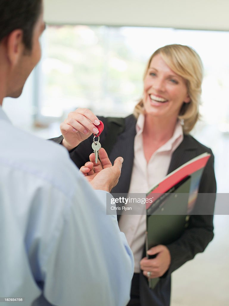 Smiling woman giving keys to man : Stock Photo