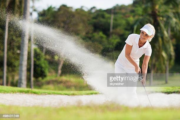 Smiling woman golf player in sand trap.