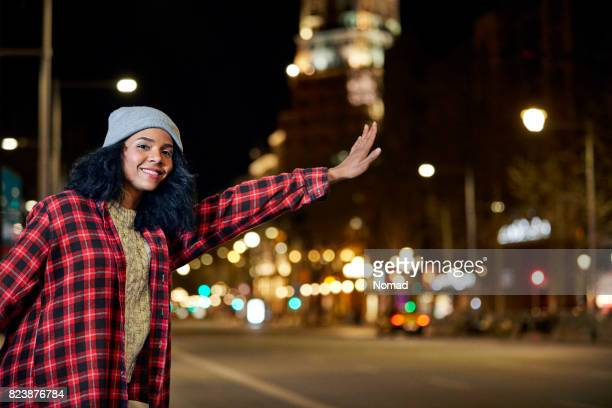 Smiling woman hailing taxi on roadside at night
