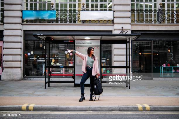 smiling woman hailing while waiting at bus stop in city - full length stock pictures, royalty-free photos & images
