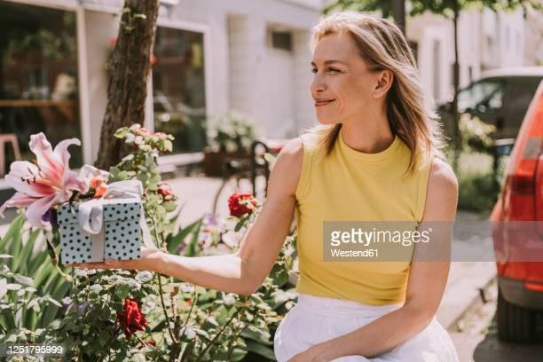 smiling woman handing over gift - gift lounge stock-fotos und bilder
