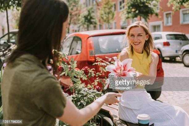smiling woman handing over gift to friend - giving stock pictures, royalty-free photos & images