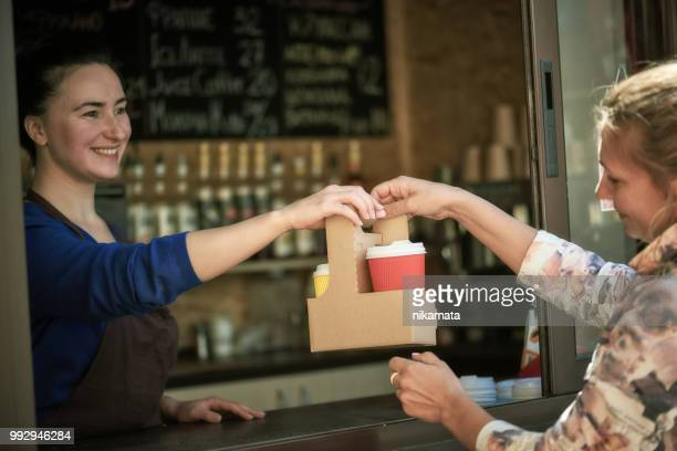 smiling woman handing takeaway coffee cups to customer at café - paper plate stock photos and pictures