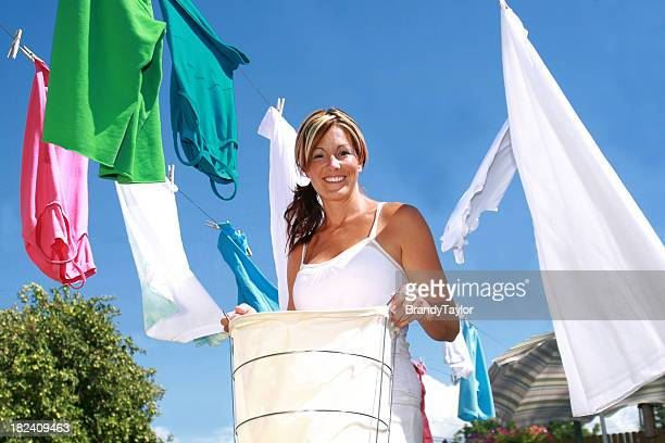 Smiling woman hanging laundry on a clothesline