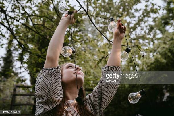 smiling woman hanging lighting equipment in yard during dinner party - hanging stock pictures, royalty-free photos & images