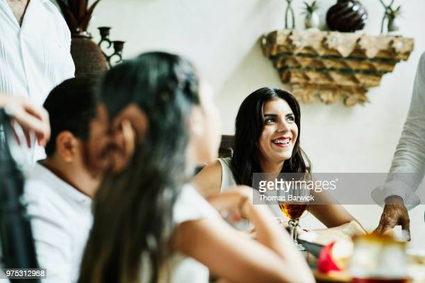 Smiling woman hanging out with family during celebration meal