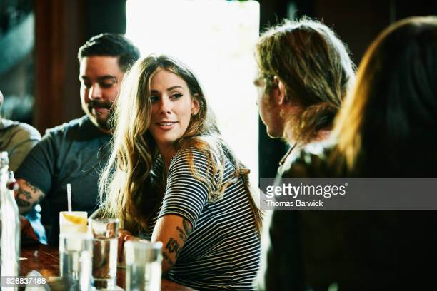 smiling woman hanging out with friend while having drinks in bar - flirtare foto e immagini stock