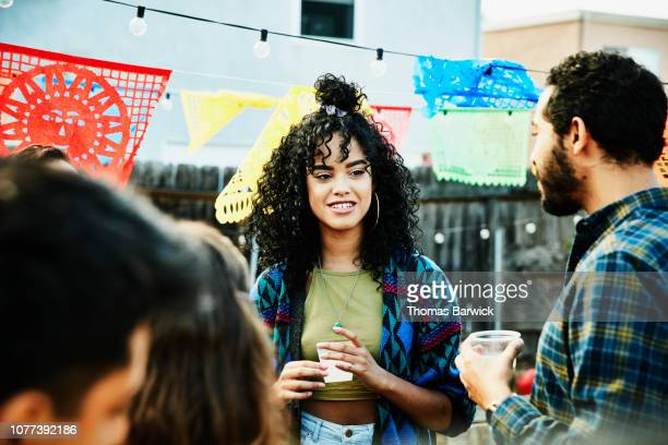 smiling woman hanging out with friends during backyard barbecue on summer afternoon - topknot stock pictures, royalty-free photos & images