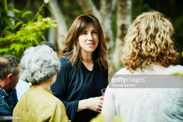 Smiling woman hanging out with friends during summer garden party