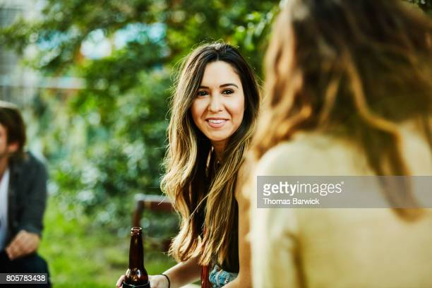 Smiling woman hanging out with friends in backyard on summer evening