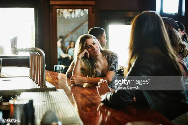 Smiling woman hanging out with friends in bar
