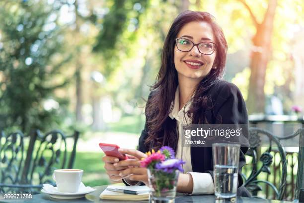 Smiling woman having a coffee and texting on her mobile