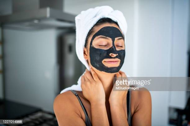 smiling woman having a spa day at home. - natural condition stock pictures, royalty-free photos & images