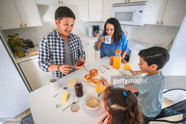 smiling woman having breakfast with family at home - family at home stock photos and pictures