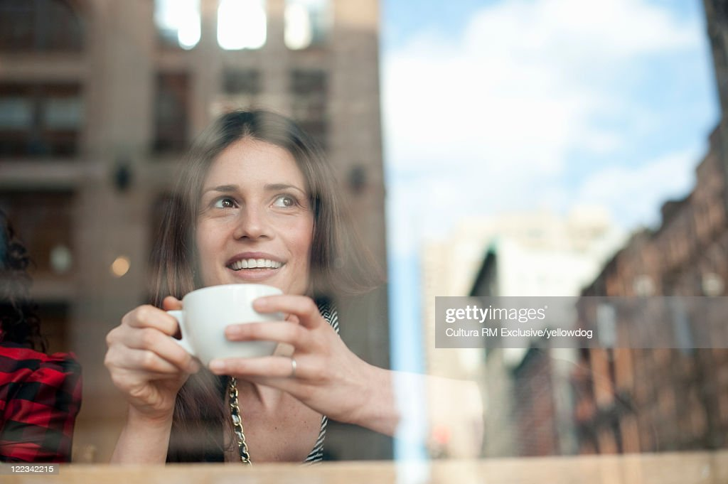 Smiling woman having coffee in cafe : ストックフォト