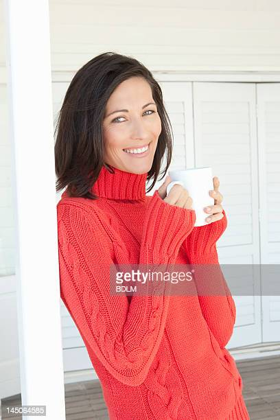 smiling woman having cup of coffee - mid adult woman sweater stock pictures, royalty-free photos & images